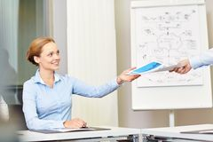 Businesswoman taking papers from someone in office Stock Photo