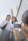 Businesswoman taking photo of her co-workers with her cell phone Royalty Free Stock Photos