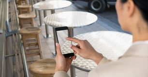 Businesswoman taking picture with mobile phone in coffee shop stock images