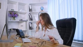 Businesswoman taking pill during work with documents in office Stock Image