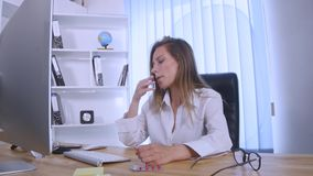 Businesswoman taking pill during work with documents in office royalty free stock image