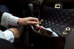 Businesswoman taking red lipstick out of handbag Royalty Free Stock Photo