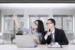Businesswoman taking selfie with partner. Happy successful businesswoman taking selfie photo with her partner while showing thumbs up in the office room Royalty Free Stock Images
