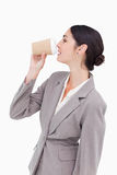 Businesswoman taking a sip out of a paper cup Royalty Free Stock Photos