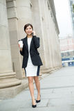 Businesswoman talk to mobile phone and walking at street Royalty Free Stock Photography