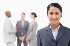 Businesswoman with talking associates behind her Stock Images