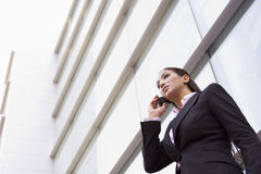 Businesswoman talking on cell phone. Outside modern office Royalty Free Stock Photos