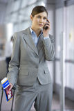 Businesswoman talking on cell phone in airport Royalty Free Stock Photos