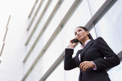 Businesswoman talking on cell phone outside. Modern office building Royalty Free Stock Image