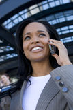 Businesswoman talking on cell phone in urban setting Stock Image