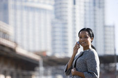 Businesswoman talking on cell phone in urban setting Stock Images