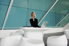 Businesswoman talking on cell telephone while sitting front of open net-book in office interior Stock Photo