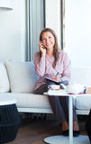 Businesswoman talking on the cellphone and writing in organizer Stock Photo