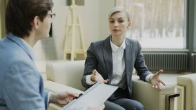 Businesswoman talking and duscussing company finance information with male business partner sitting on armchair in. Modern office indoors stock footage