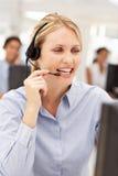 Businesswoman talking into headset. Businesswomen talking into headset smiling Royalty Free Stock Photo