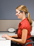 Businesswoman talking on headset at desk Stock Images
