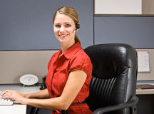 Businesswoman talking on headset at desk Stock Photo
