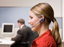 Businesswoman talking on headset at desk Stock Image