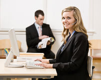 Businesswoman talking on headset at desk Royalty Free Stock Photo