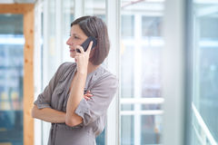 Businesswoman talking on her phone in a brightly lit corridor Stock Image