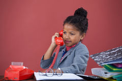 Businesswoman talking on land line. While sitting at table against orange background Royalty Free Stock Photos