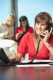 Businesswoman talking on landline phone Stock Photos