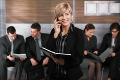 Businesswoman talking on mobile. Happy young businesswomen standing in office hallway, holding personal organizer, talking on mobile phone Royalty Free Stock Photos