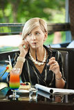 Businesswoman talking on mobile in cafe Stock Images