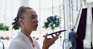 Businesswoman talking on mobile mobile phone while standing near escalator in 4k. Side view of Caucasian Businesswoman talking on mobile mobile phone while stock footage