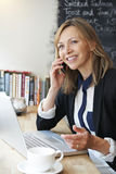Businesswoman Talking On Mobile Phone In Cafe Stock Photography