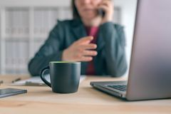Businesswoman talking on mobile phone during coffee break from office stock photos