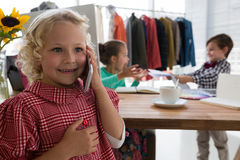 Businesswoman talking on mobile phone while colleagues working in background Royalty Free Stock Images