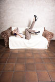 Businesswoman talking on mobile phone on couch Royalty Free Stock Images