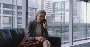 Businesswoman talking on mobile phone in the lobby at office 4k. Front view of caucasian businesswoman talking on mobile phone in the lobby at office. She is stock video footage