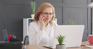 Businesswoman talking on mobile phone. Mature businesswoman talking on mobile phone and using laptop at office stock video