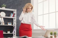 Businesswoman talking on mobile phone at office. Serious ceo businesswoman talking on mobile, having problems while working on laptop in modern office, copy Stock Photography
