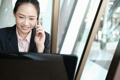 Businesswoman talking on mobile phone at office. young female en royalty free stock images