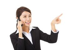 businesswoman talking on the mobile  phone and pointing Royalty Free Stock Image