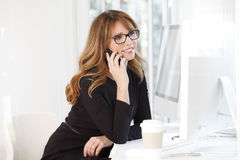 Businesswoman talking on mobile phone. Portrait of an attractive financial manager sitting at office in front of computers and making call while drinking coffee Royalty Free Stock Photo