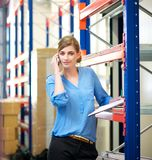 Businesswoman talking on mobile phone in warehouse Royalty Free Stock Image