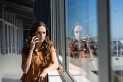 Businesswoman talking on mobile phone by window at office stock images