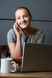 Businesswoman Talking On Mobile Phone Working On Laptop In Inter Royalty Free Stock Image