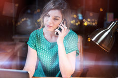 Businesswoman talking on mobile phone while working on laptop Royalty Free Stock Photography