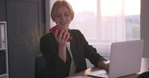 Businesswoman using mobile phone and laptop at office. Businesswoman talking on mobile phone and working on laptop at office stock video footage