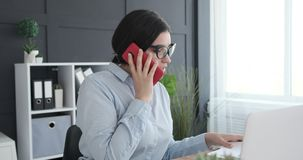 Businesswoman talking on mobile phone while working at office. Businesswoman doing paperwork and talking on mobile phone at office stock video footage