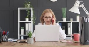 Businesswoman talking on mobile phone at workplace stock footage