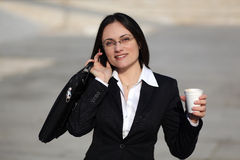 Businesswoman talking onthe phone. Business woman talking on the phone while holding coffee Royalty Free Stock Photo
