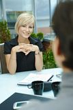 Businesswoman talking outdoor. Happy young businesswoman sitting outdoor on office terrace and talking, smiling. Over the shoulder view Stock Images