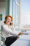 Businesswoman talking over mobile phone. Confident businesswoman talking over mobile or smart phone while having break. Red haired woman looking at window and Royalty Free Stock Image