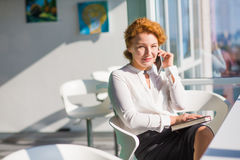 Businesswoman talking over mobile phone. Businesswoman discussing burning problems and issues with partners over mobile phone. Red haired lady smiling and Royalty Free Stock Photography